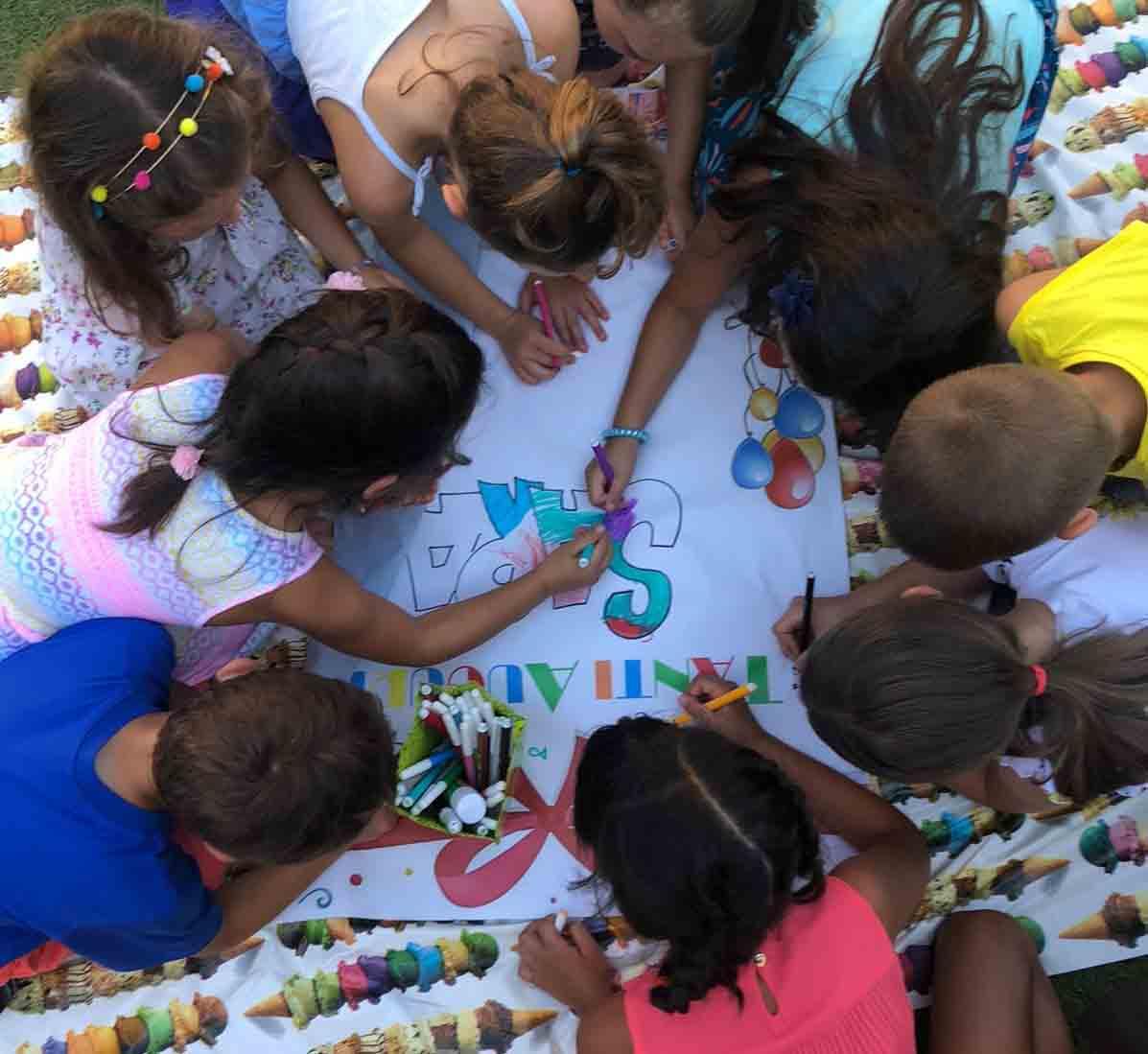 Bambini che decorano il cartellone di buon compleanno